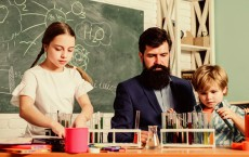 School clubs interactive education. Teacher and pupils test tubes in classroom. After school clubs are great way to develop kids in different areas. Clubs for preschoolers. Chemistry experiment - stock image